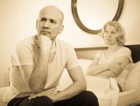 Sad elderly man and frustrated mature woman sorting out relationships in bed