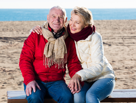 Aged husband and wife sitting together on bench by sea on chilly day Stock Photo