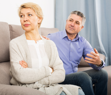 Mature husband and wife quarrels with each other at clarification of the family relation in home Stock Photo