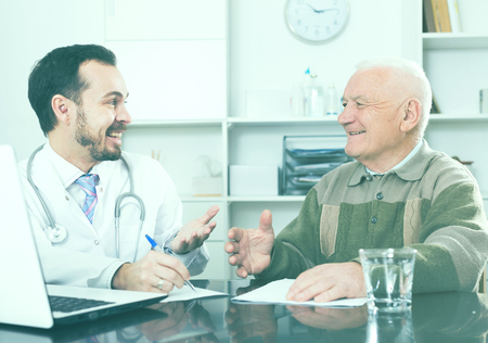 Mature man having consultation with male doctor in hospital