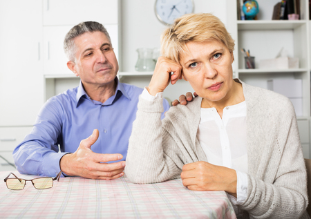 Senior couple find out relationship and sort out family problems in home interior