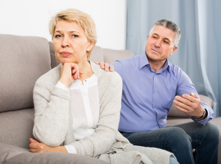 resentful mature couple quarreling at home with each other and take offense