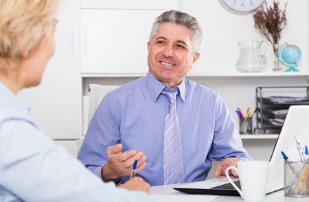 Mature chief gives task to subordinate at office at table