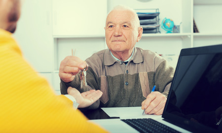 Old man and agent sign lease contract of apartment in agency
