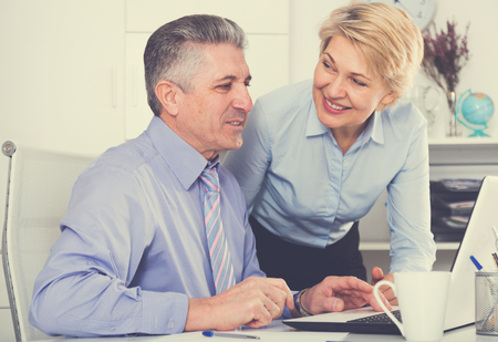 Mature employees looking at interesting news on internet at computer