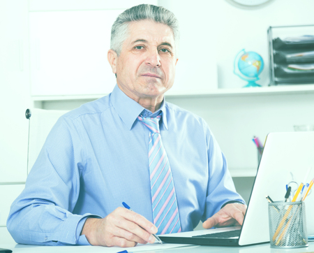 Mature lawyer preparing important documents on computer at legal consultation office