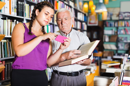Young girl with phone in books shop and grandfather choosing new book