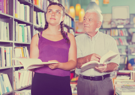 Grandfather with granddaughter are reading books in bookstore Stockfoto