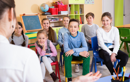 Portrait of  friendly smiling positive  pupils listening teacher at lesson in elementary school
