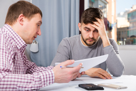 Man having problems with some documents, worriedly discussing with friend at home table Stock Photo