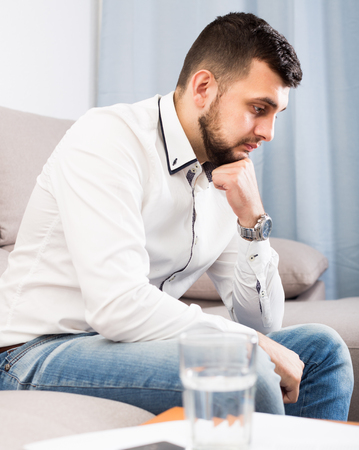 Sad young male spending day alone at home Stock Photo