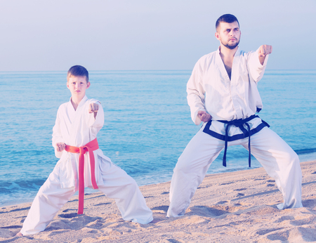 Adult man and boy exercising karate in morning outdoor