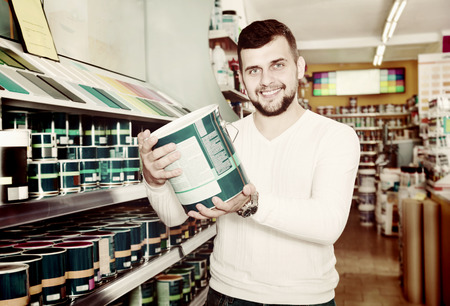 Male customer examining various wall paints in a paint supplies store