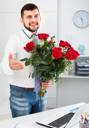 Young happy man ready to present flowers to woman in office