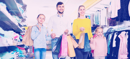 Young cheerful positive smiling parents with two little girls shopping in mall, carrying purchases Stock Photo