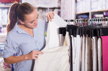 Young female shopper searching for fabric in textile shop
