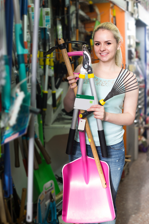 adult woman selecting gardening equipment in household department