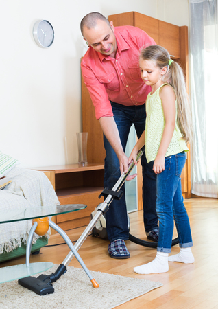 Happy dad and his cute little daughter hoovering in the living room together  Stock Photo