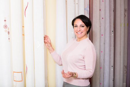 Positive female customer posing near undercurtain fabric inside textile store