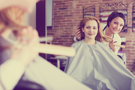 Happy young woman consults with master in hairdress salon about hair cutting