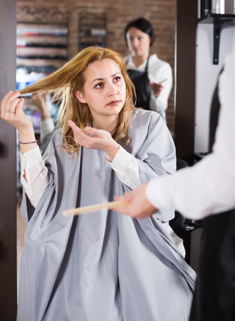 Dissatisfied ordinary woman is upset by her haircut and master in hairdress salon