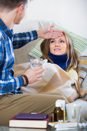 spanish woman with cold lying on couch, boyfriend taking care  Stock Photo