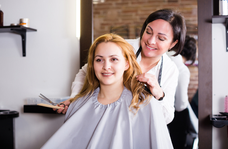 Aged hairdresser is doing fashionable haircut to young woman with scissors and comb in hairdress salon.