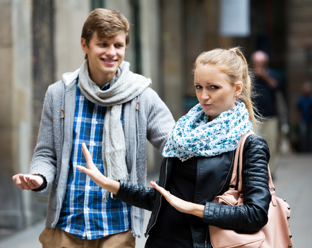 Unhappy blonde cannot get rid off bothering admirer outdoors. Focus on the woman
