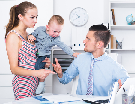 Angry mother and little boy quarreling with adult banker in office