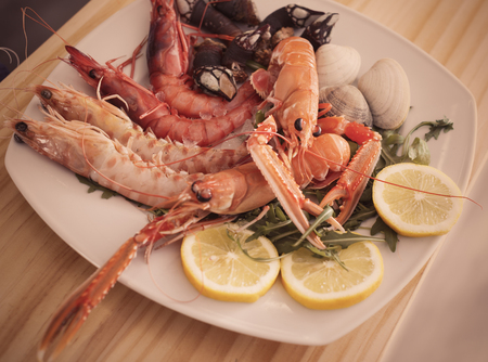 Gourmet restaurant seafood dish with langoustines, shrimps and clams decorated arugula and lemon Stock Photo