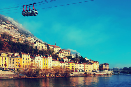 Cityscape of Grenoble with Bastille hill and famous cable car in winter, France