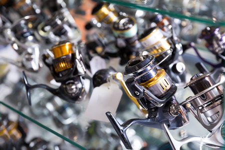 Image of stand with nice baitcasting reel for rod in the sports shop Stock Photo