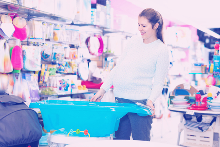 Happy  positive  pregnant woman is choosing baby bath in the shop.