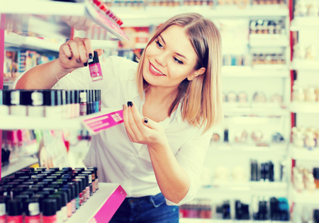 Smiling girl  looking new nail polishes in cosmetics store