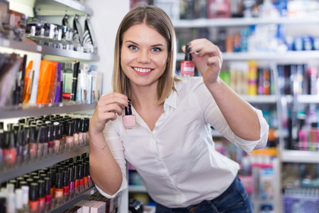 Young woman looking for new stylish color of a nail varnish in the cosmetic shop