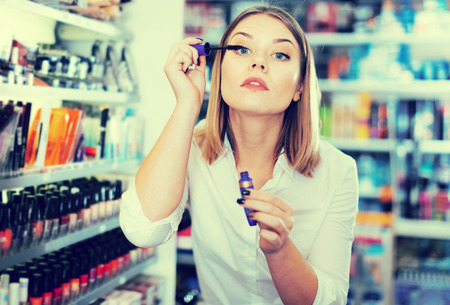 Attractive young woman testing mascara in cosmetics store
