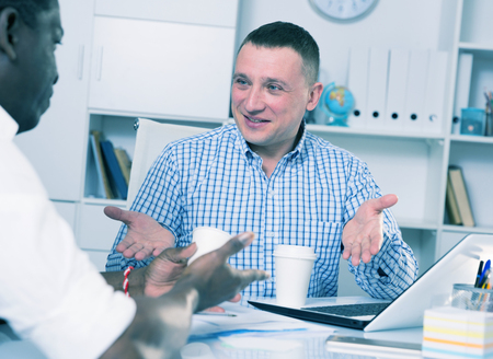 Happy man talking with male coworker and drinking coffee at workplace in office