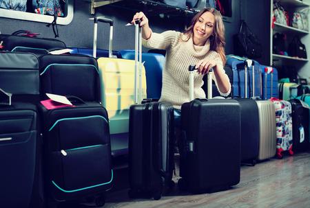 Glad cheerful female customer choosing travel suitcase in haberdashery shop