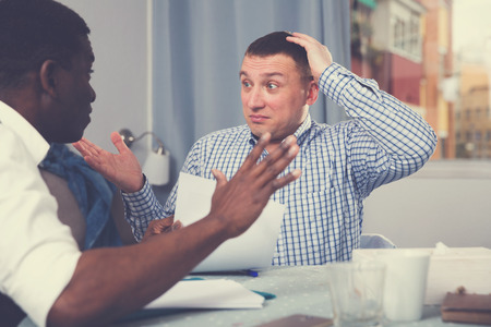 Troubled man discussing documents with male partner while sitting at home table