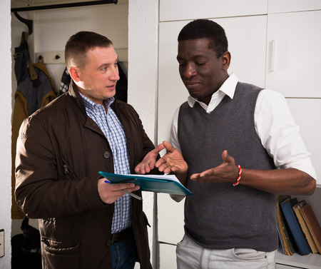 Friendly landlord visiting tenant apartment, signing agreement with positive man