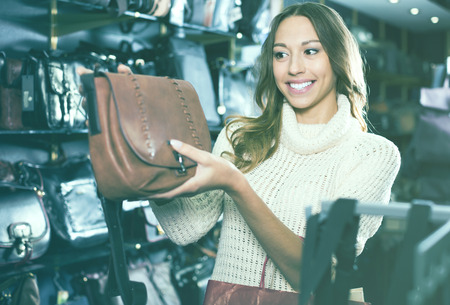 Satisfied woman customer holding new hand bag in store