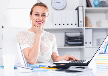 Cheerful businesswoman in shirt working at the computer