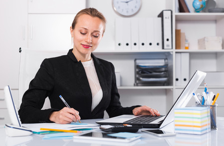 Young and smiling businesswoman in suit filling up documents Foto de archivo