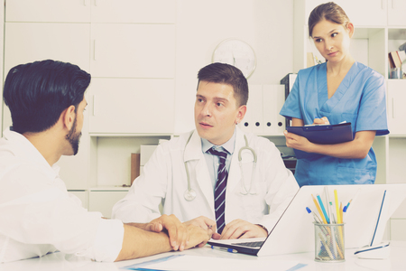 Portrait of confident male doctor listening to patient complaints at clinic