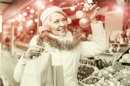 Positive mature female  in Christmas hat  buying decoration at  Fair outside Stock Photo