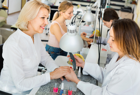 Two  positive women clients having manicure done in nail salon