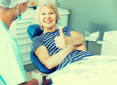 Portrait of smiling satisfied woman visiting dentist giving thumbs up in the dental clinic