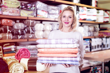 Adult girl customer showing bought home textiles in textile shop Stock Photo