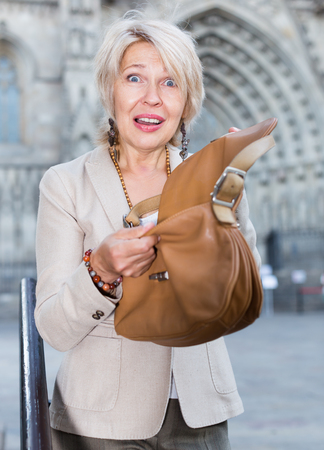 Mature female is displeased of theft from her bag on the street.