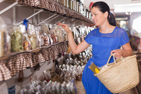 young glad woman choosing herbs and spices in biofood shop